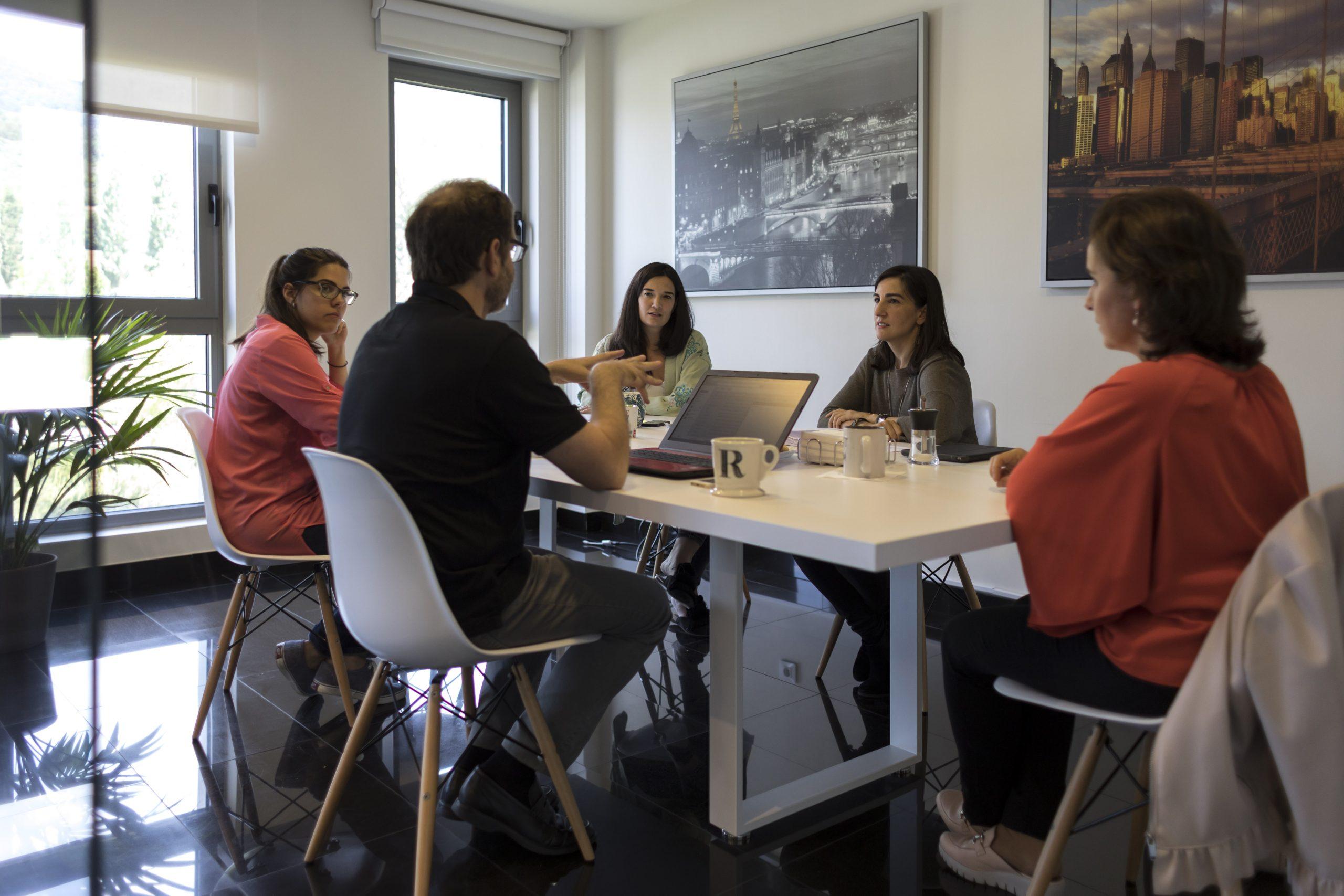 Equipo de 5 personas en una mesa compartiendo ideas