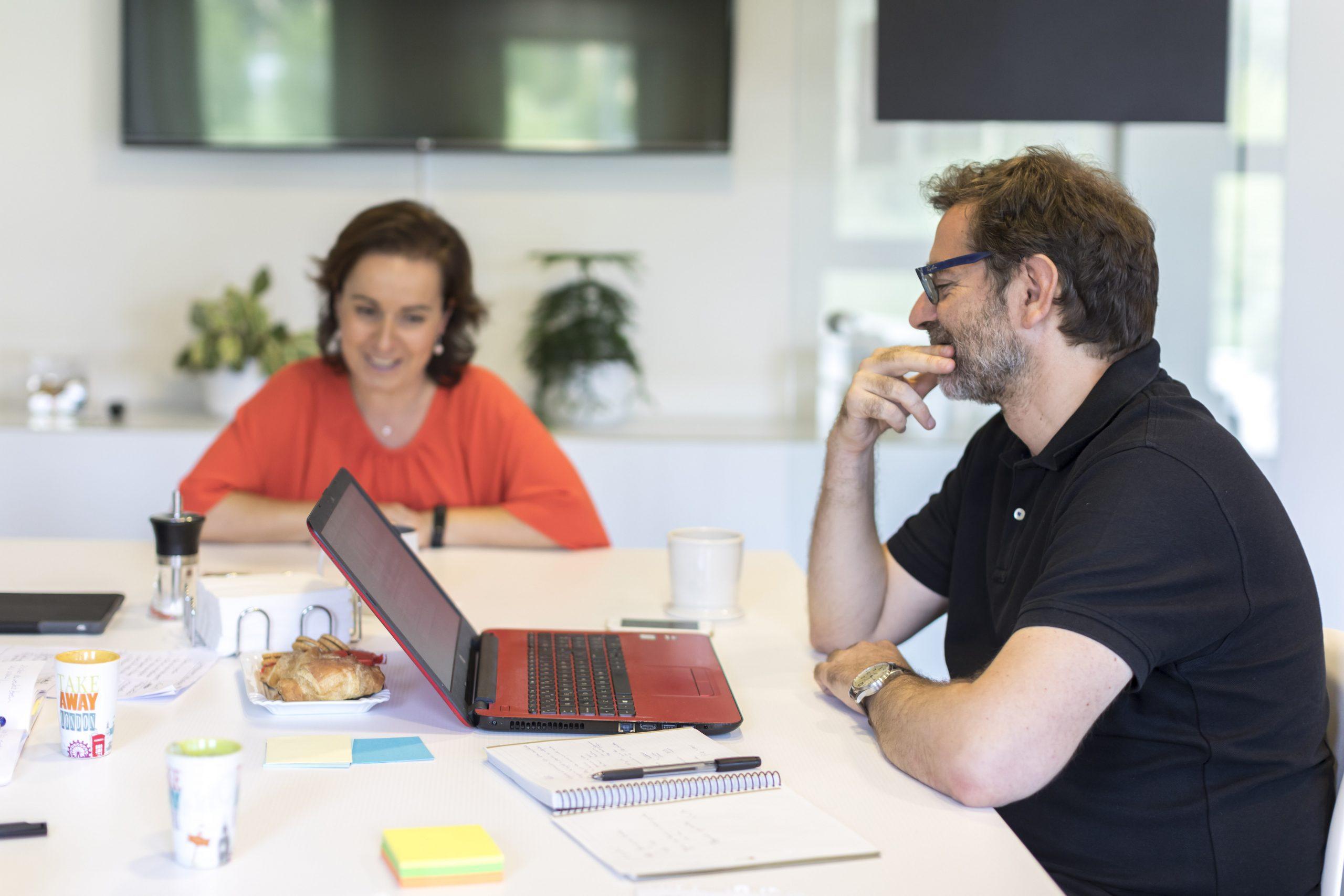 Dos personas en una reunión con el ordenador