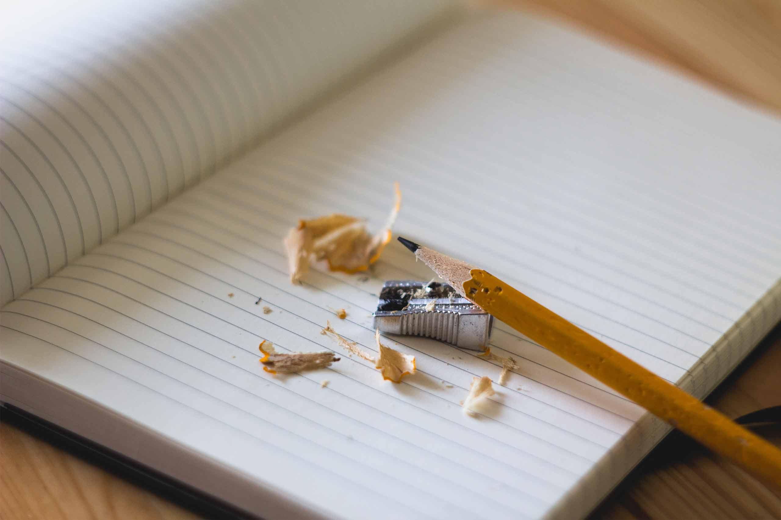 lápiz con sacapuntas y cuaderno del colegio