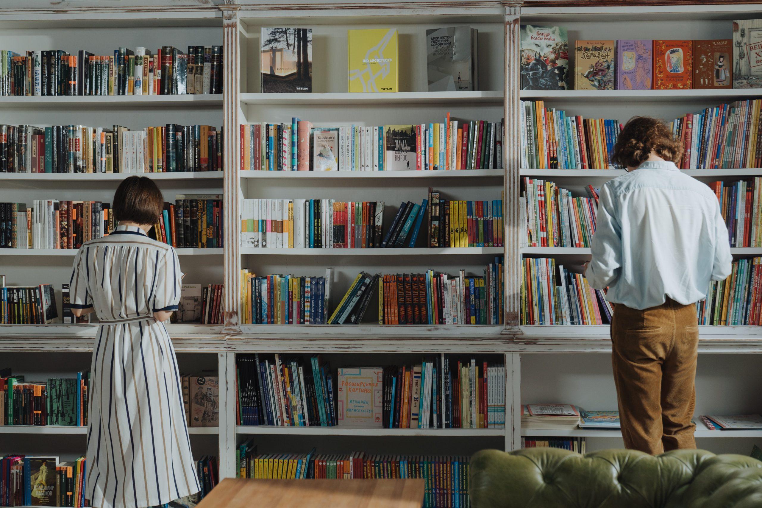 Dos personas documentándose frente a unas estanterías llenas de libros