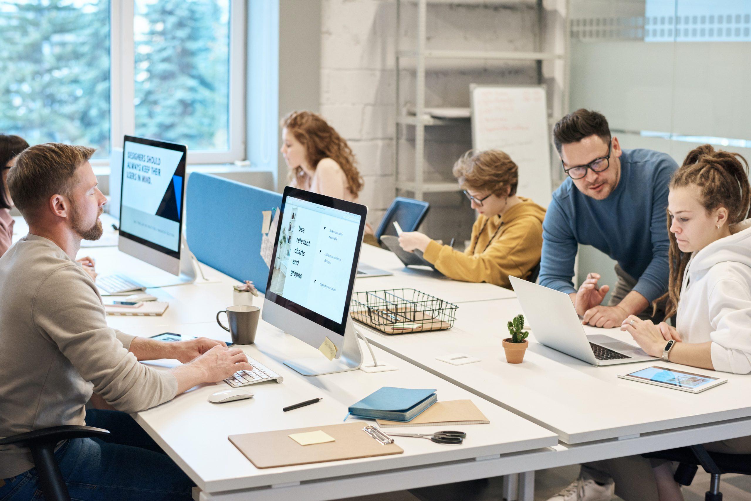 Equipo documentándose y dialogando frente a los ordenadores de su oficina