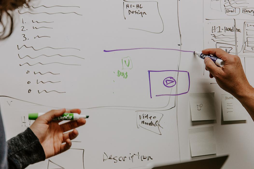 dos personas escribiendo en pizarra esquema de web de colegio
